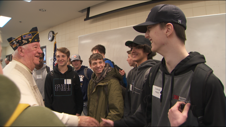 Veteran Ed Riveness (far left) shakes hands with students at Hastings High School who first befriended Riveness' friend Loren Mollet.
