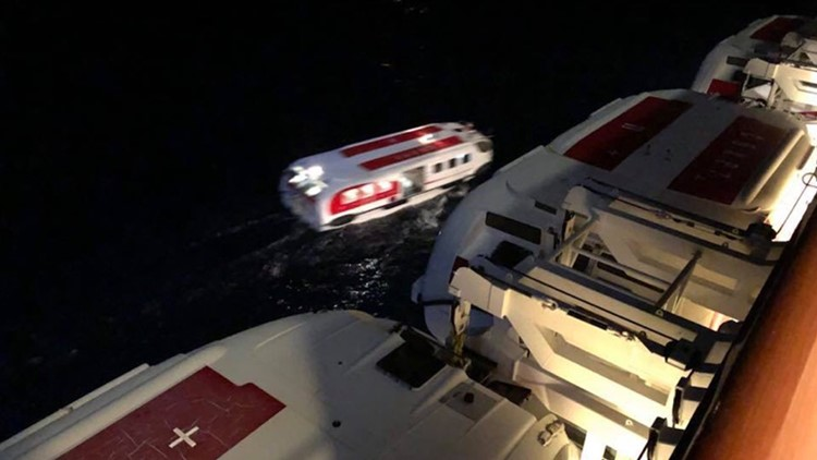 A life boat searches for a cruise ship passenger who fell overboard.