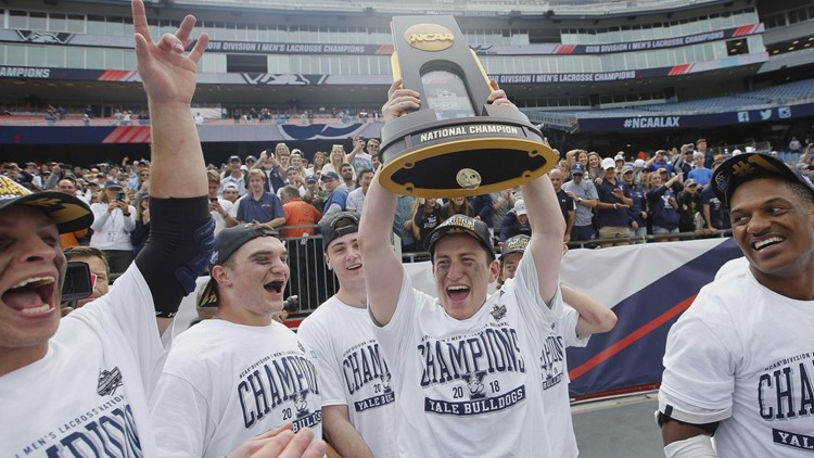 Yale midfielder Jack Tigh (18) holds up the trophy after Yale's 13-11 win over Duke in the men's NCAA lacrosse championship game at Gillette Stadium.